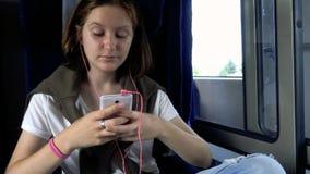 Tienermeisje met smartphone bij trein stock videobeelden