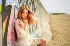 Tienermeisje op een graffiti behandelde muur bij het strand Stock Foto
