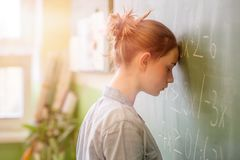 Tienermeisje in wiskundeklasse door de wiskundeformule die wordt overweldigd Stock Foto's