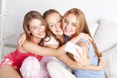 Tienermeisjes die met smartphone selfie thuis nemen stock foto
