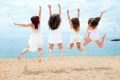 Tienermeisjes die op strand springen Stock Foto