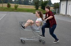 Tienermeisjes die pret met boodschappenwagentje hebben Royalty-vrije Stock Afbeeldingen
