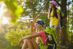 Tienermeisjes met rugzak die in bosreis en toerismeconcept rusten stock fotografie