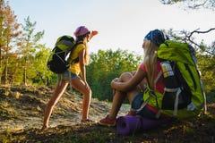 Tienermeisjes met rugzak die in bosreis en toerismeconcept rusten stock afbeelding