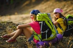 Tienermeisjes met rugzak die op zand rusten Het concept van de reis en van het toerisme royalty-vrije stock afbeelding