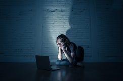 Tienermens die de intimidatie aan zitting van Internet cyber alleen met computer lijden die hopeloos voelen stock fotografie