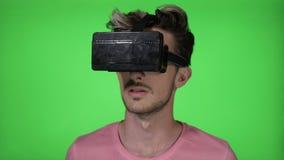 Tienermens die voor het eerst een verbazende ervaring van virtuele werkelijkheid ervaren die VR-hoofdtelefoongadget op het groene stock footage