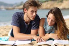 Tienerpaar of vriendenstudenten die op het strand bestuderen stock afbeeldingen