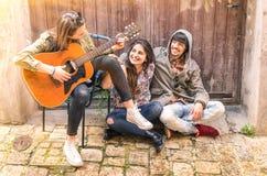 Tieners beste vrienden die gitaar in openlucht spelen Stock Foto