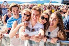 Tieners bij het festival van de de zomermuziek in menigte die selfie nemen royalty-vrije stock afbeelding