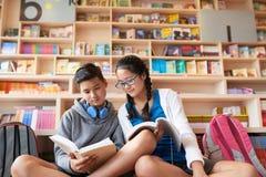 Tieners die in bibliotheek samen bestuderen royalty-vrije stock fotografie