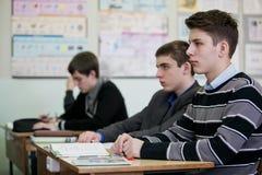 Tieners die bij één bureau zitten en aan hun leraar luisteren stock foto