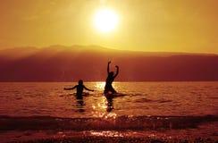 Tieners, die bij zonsondergang baden Stock Afbeelding