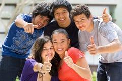 Tieners die buiten school stellen Stock Foto