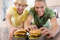 Tieners die Burgers eten stock afbeeldingen