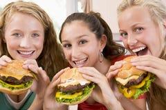 Tieners die Burgers eten royalty-vrije stock afbeelding