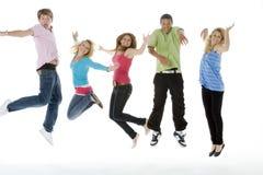 Tieners die in de Lucht springen Stock Afbeeldingen