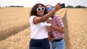 Tieners die koffie drinken en selfies op hun smartphones voor sociale media nemen stock videobeelden