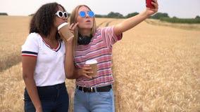 Tieners die koffie drinken en selfies op hun smartphones voor sociale media nemen stock video
