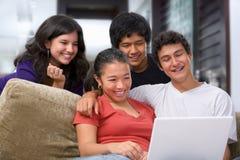 Tieners die op iets op laptop letten Royalty-vrije Stock Afbeeldingen