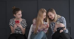 Tieners die pret hebben terwijl tekstberichten op mobiele telefoons stock videobeelden