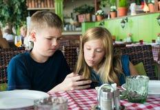 Tieners die pret met mobiele telefoons in koffie hebben Modern levensstijl en technologieconcept Kinderen die in restaurant zitte stock fotografie