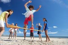 Tieners die pret op strand hebben Stock Foto