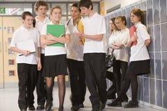 Tieners die rond een meisje op school worden gegroepeerd Stock Foto