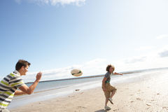 Tieners die Rugby op Strand samen spelen Stock Foto's