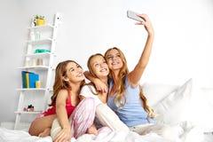 Tieners die selfie door smartphone thuis nemen stock afbeeldingen