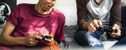Tieners die uit in slaapkamer het spelen videospelletjes samen hangen stock foto's