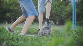 Tieners die voetbalvoetbal spelen in openlucht, jongens die van actieve hobby in park, langzame motie genieten stock video