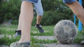 Tieners die voetbalvoetbal spelen in openlucht, jongens die van actieve hobby in park, langzame motie genieten stock footage
