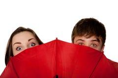 Tieners, een jongen en een meisje, die voor de rode paraplu piepen. royalty-vrije stock afbeelding