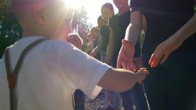 Tieners en kinderenteams die elkaar met schokhanden begroeten bij de zomer zonnige dag stock videobeelden