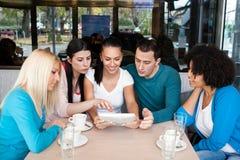 Tieners in koffie met tablet stock afbeelding