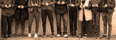 Tieners met telefoons tegen muur royalty-vrije stock fotografie