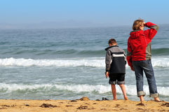 Tieners op het de lente overzeese strand stock afbeelding