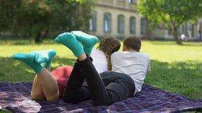Tienersbenen in gelijkaardige comfortabele sokken, die op plaid in park, textiel liggen stock videobeelden
