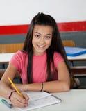 Tienerschoolmeisje die in Boek schrijven royalty-vrije stock afbeelding