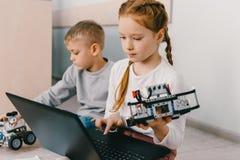 tienerschoolmeisje programmeringsrobot terwijl het zitten op vloer royalty-vrije stock foto