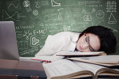 Tienerschoolmeisjeslaap op bureau Stock Foto's