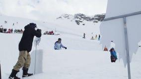 Tienerskiër in de rit van het pluchekostuum op springplank Kartonvoorwerpen cameraman stock videobeelden
