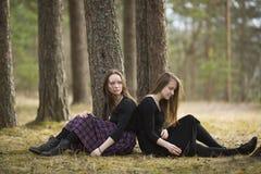 Tienersmeisjes die pensively op de grond in de bosaard zitten royalty-vrije stock foto's