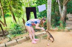 Tienerspelen met puppy in groene werf stock fotografie