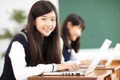 Tienerstudent die online met laptop in klaslokaal leren stock foto's