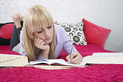 Tienerstudent Writing In Book op Bed royalty-vrije stock fotografie