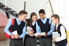 Tienerstudenten in modieuze eenvormige school stock afbeeldingen