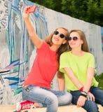 Tienersvrienden in hipsteruitrusting die pret hebben in openlucht en stock afbeeldingen