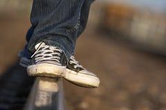 Tienertennisschoenen die op de sporen van de spoorweg in evenwicht brengen stock fotografie